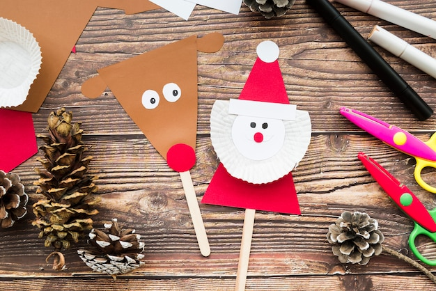 Reindeer and santa claus prop with paper; pinecone; scissor and felt-tip pen on wooden desk Free Photo
