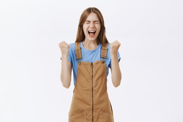 Радуясь победе счастливой молодой женщины, празднуя победу, крича да доволен Бесплатные Фотографии