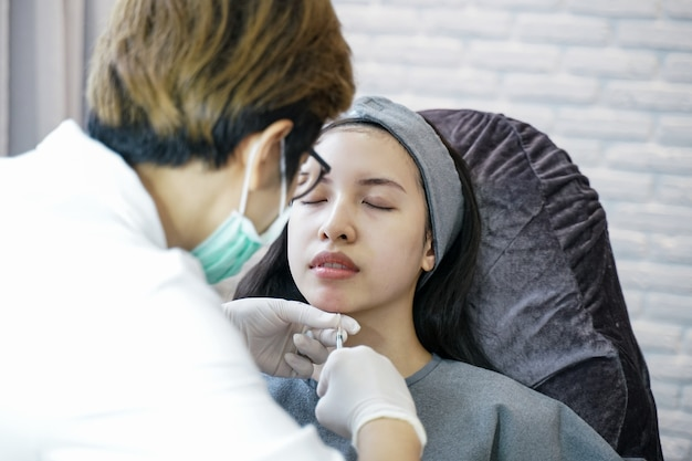 Rejuvenation procedure in beauty clinic injection. women injection in her chin. Premium Photo