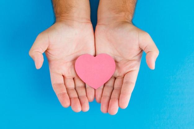 Concetto di relazione sulla disposizione blu del piano della tavola. mani che tengono il cuore di carta tagliata. Foto Gratuite