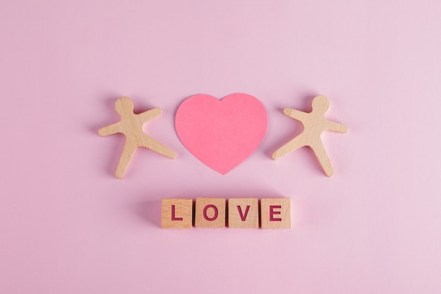 Relationship concept with paper cut heart, wooden cubes, human models on pink table flat lay. Free Photo
