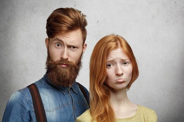 Концепция проблемы отношений. красивая рыжая молодая женщина надувает губы, выглядя расстроенными и несчастными со своим парнем. Бесплатные Фотографии