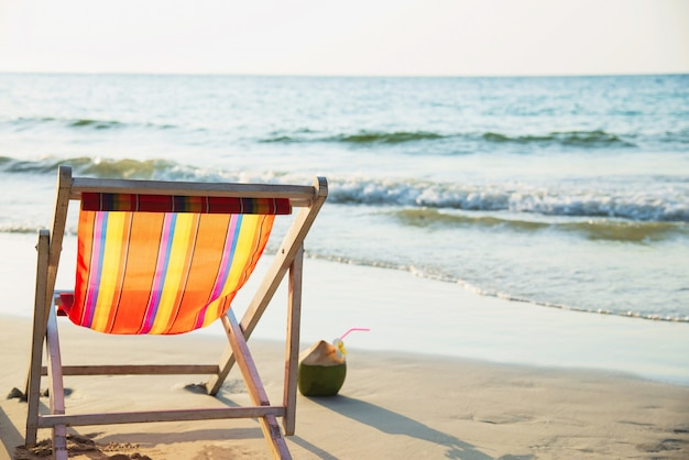Relax beach chair with fresh coconut on clean sand beach with blue sea and clear sky - sea nature relax concept Free Photo