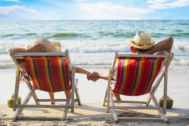 Relax couple lay down on beach chiar with sea wave - man and woman have vacation at sea nature concept Free Photo