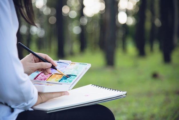Relax woman painting watercolor art work in green garden forest nature Free Photo