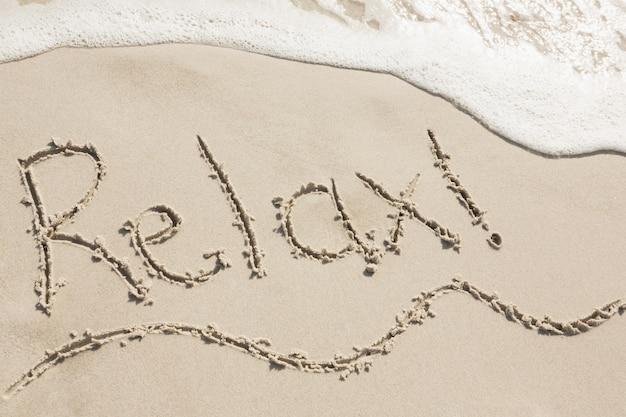 Relax scritta sulla sabbia Foto Gratuite