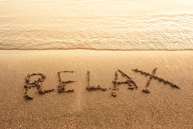 Relax written on sand Free Photo