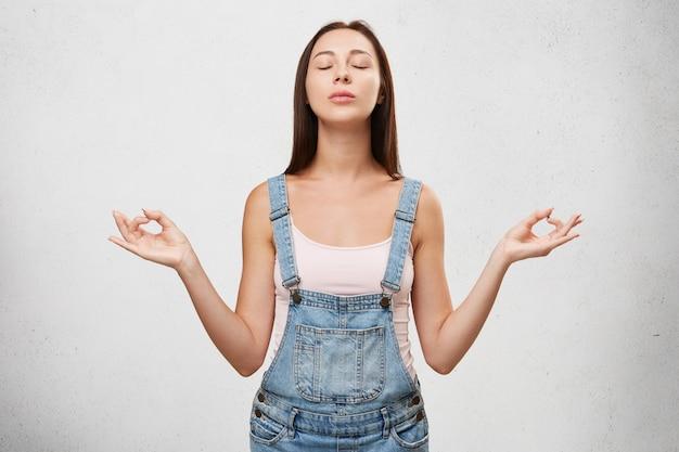 Концепция релаксации и медитации. красивая молодая самка медитирует с закрытыми глазами после занятий йогой по утрам, расслабляет тело и очищает ум, готовит себя к новому счастливому дню Бесплатные Фотографии