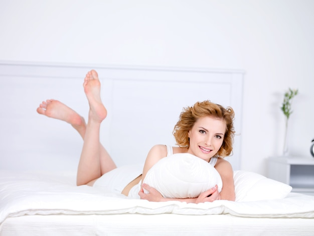 Relaxation for young beautiful smiling woman lying in a bed with pillow Free Photo
