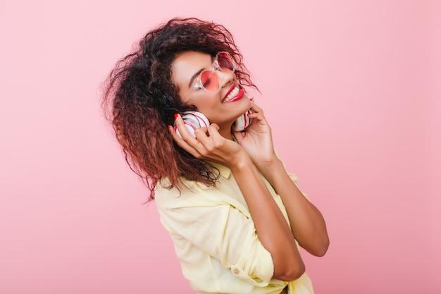 Donna africana rilassata con musica d'ascolto della pelle marrone chiaro con gli occhi chiusi e l'espressione del viso felice. ragazza nera riccia alla moda in camicia di cotone gialla che tiene gli auricolari e sorridente Foto Gratuite