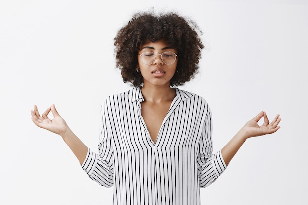 Relaxed attractive modern african american female businesswoman leading tiresome lifestyle gathering patience in yoga closing eyes, spreading hands in zen gesture Free Photo