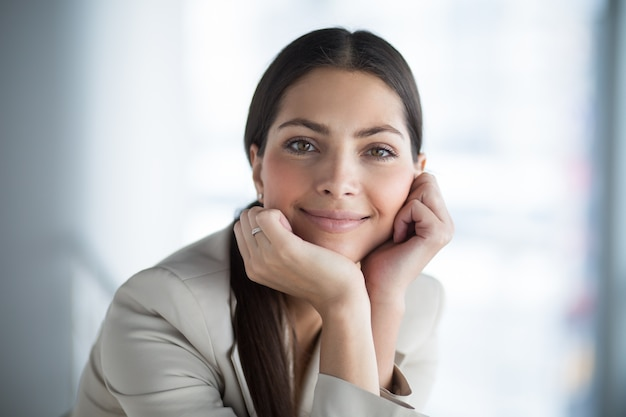 Relaxed beautiful business lady leaning on hands Free Photo