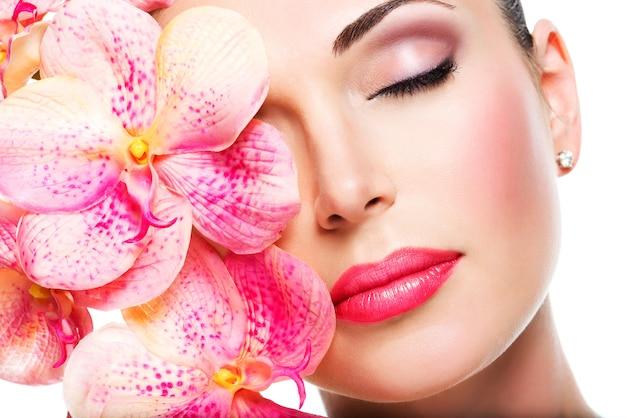 Расслабленное красивое лицо молодой девушки с чистой кожей и розовыми орхидеями. концепция лечения красоты Бесплатные Фотографии