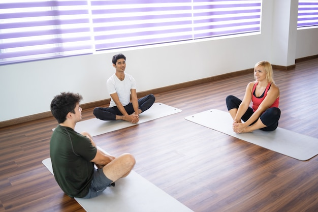 Relaxed beginners sitting on mats and stretching legs Free Photo