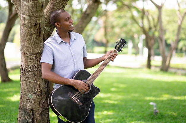 Relaxed black man playing guitar and leaning on tree Free Photo