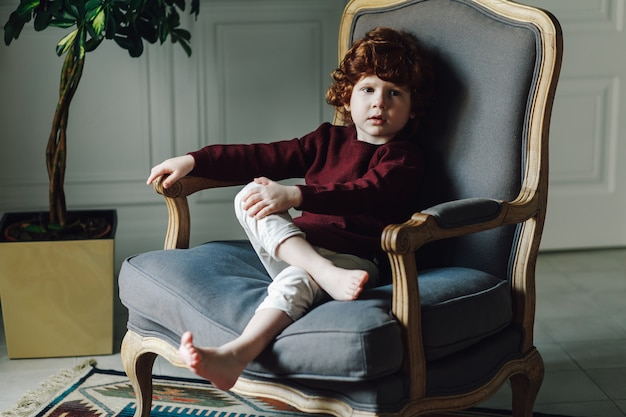 Relaxed boy child in comfortable armchair posing in vintage interior Premium Photo