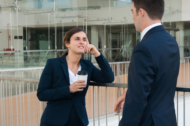 Relaxed business man and woman chatting outdoors Free Photo