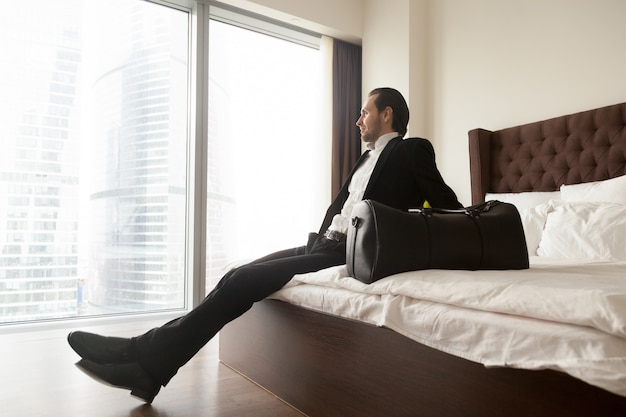 Relaxed businessman sitting on bed besides luggage bag. Free Photo