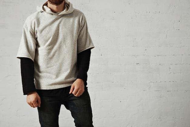 Расслабленный, спокойный спортивный молодой человек с бородой в черных джинсах, черной футболке с длинным рукавом и простой удобной толстовке с капюшоном серого цвета вереска, изолированной на белом Бесплатные Фотографии
