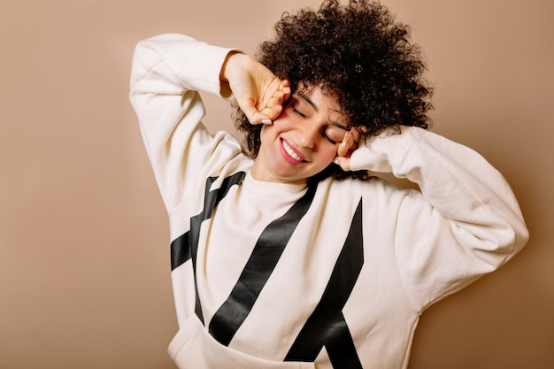 Relaxed charming girl with curls wearing white pullover smiling with closed eyes and stretching over isolated wall Free Photo