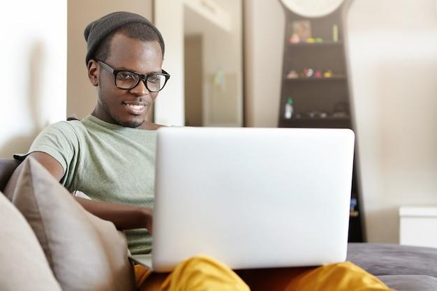 スタイリッシュなアイウェアと帽子を自宅で快適なソファに座ってラップトップpcを膝の上に置いてリラックスした陽気な若い黒人ヨーロッパ人 無料写真