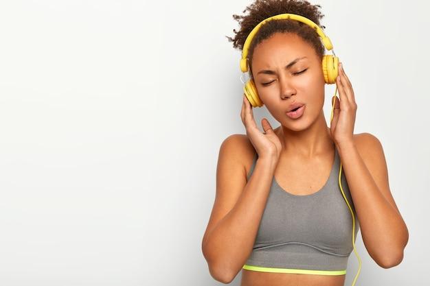 Ragazza sportiva dai capelli ricci rilassata, si allena al coperto, canta canzoni, ascolta musica in cuffia, indossa un top grigio Foto Gratuite