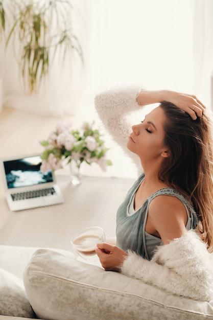 Расслабленная девушка дома пить кофе. внутренний мир. девушка удобно сидит на диване и пьет кофе. Premium Фотографии