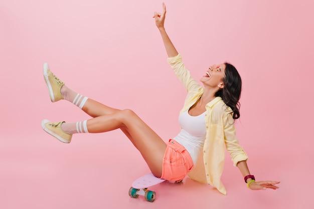 Ragazza rilassata in abito estivo luminoso seduto su skateboard con le gambe in alto e ridendo. bella giovane signora castana in scarpe gialle che trascorrono del tempo con il longboard. Foto Gratuite