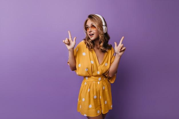 音楽を聴き、踊るオレンジ色の服装でリラックスした女の子。ヘッドフォンで紫にポーズをとるjocund白人の若い女性。 無料写真