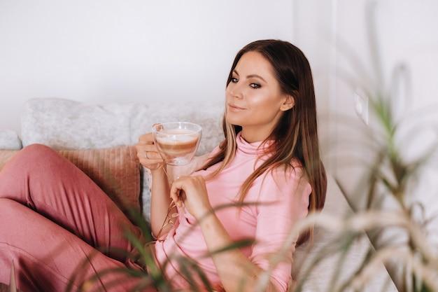 Расслабленная девушка утром в пижаме дома пьет кофе. внутренний мир. девушка удобно сидит на диване и пьет кофе, о чем-то мечтает. Premium Фотографии