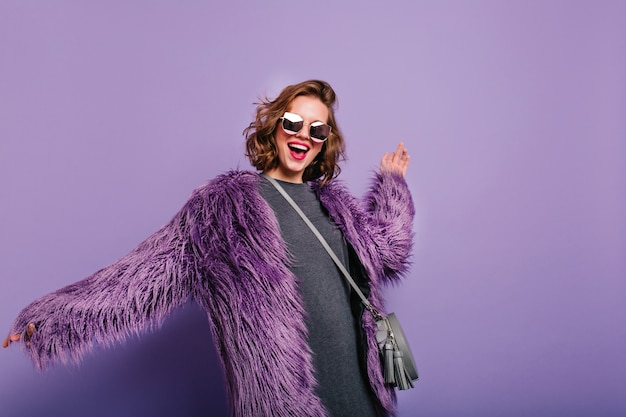 紫色の背景に自信を持ってポーズで立っている灰色の財布を持つリラックスした女の子 無料写真
