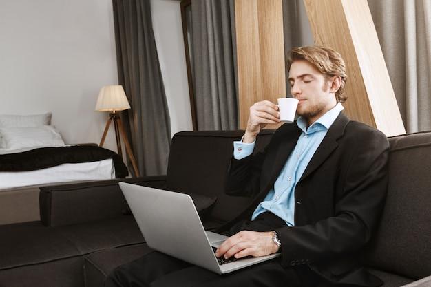 Расслабленный красивый бизнесмен с прической sylish и борода, сидящая в гостиничном номере, выпивая кофе, работая над новым проектом запуска. удобное рабочее место Бесплатные Фотографии
