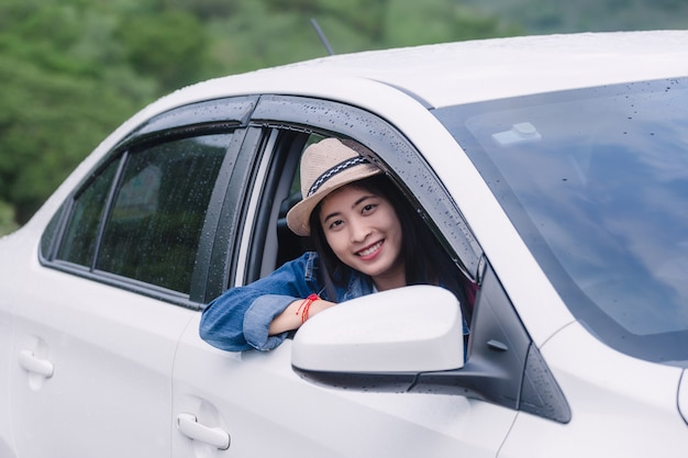 Relaxed happy woman on summer road trip travel vacation looking at nature view out car window Premium Photo