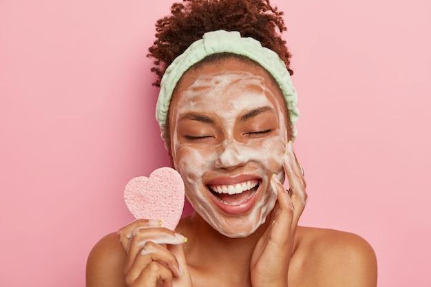 편안하고 즐거운 어두운 피부의 여성 모델은 비누 거품으로 얼굴을 씻고, 만족스러운 세션을 즐기고, 즐거움에서 눈을 감고, 화장품 스폰지를 들고, 몸을 돌보고, 실내에서 알몸으로 서 있습니다. 무료 사진