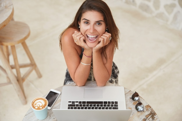 リラックスしたうれしそうな女性のフリーランサーは、クライアントプロジェクトで作業し、ソフトウェアを更新し、ワイヤレスインターネットに接続されたコーヒーショップで作業します。 無料写真