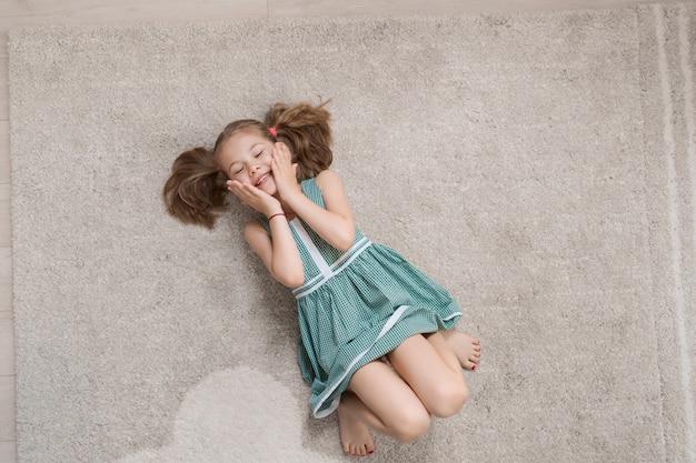 Bambina rilassata sdraiato sul pavimento in casa e sorridente Foto Gratuite