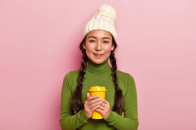 Bella donna dai capelli scuri rilassata con due trecce, tiene caffè da asporto, si riscalda durante la giornata invernale con bevanda calda, indossa un cappello bianco e dolcevita verde Foto Gratuite