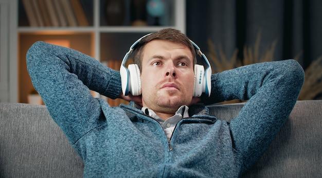 Расслабленный мужчина наслаждается музыкой в беспроводных наушниках, откидываясь назад на диване с руками за головой Premium Фотографии