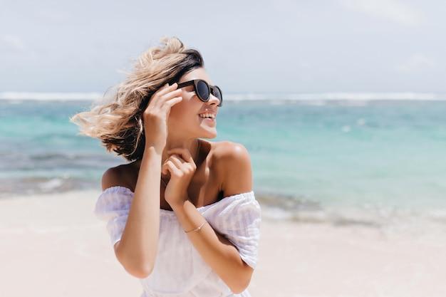 Расслабленная короткошерстная женщина позирует на пляже. открытый выстрел веселой молодой леди в солнцезащитных очках, наслаждаясь отдыхом. Бесплатные Фотографии