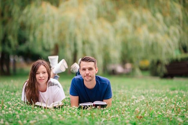 草の上に横たわっている間本を読んでリラックスした若いカップル Premium写真