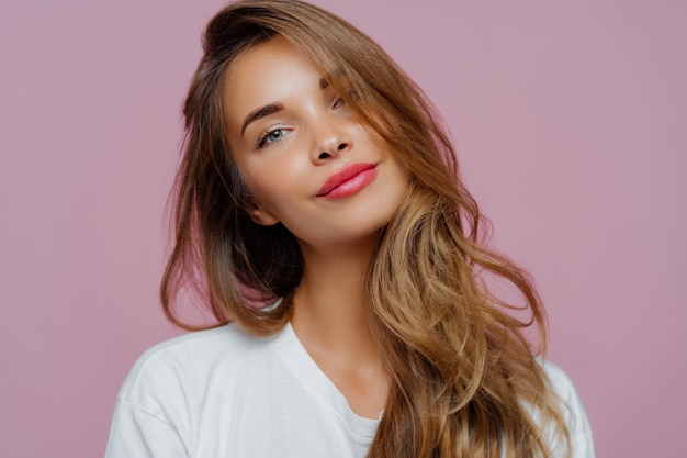 Relaxed young female model tilts head, has makeup, fair hair, dressed in white clothes Premium Photo