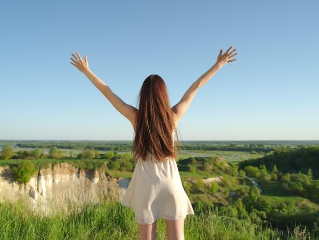 자연에서 야외에서 제기 팔으로 편안한 젊은 행복 한 여자. 어린 소녀는 하늘까지 올려 진 그녀의 팔을 의미합니다. 여름을 즐기는 절벽에 의해 서 평화로운 소녀. -야외 무료 사진