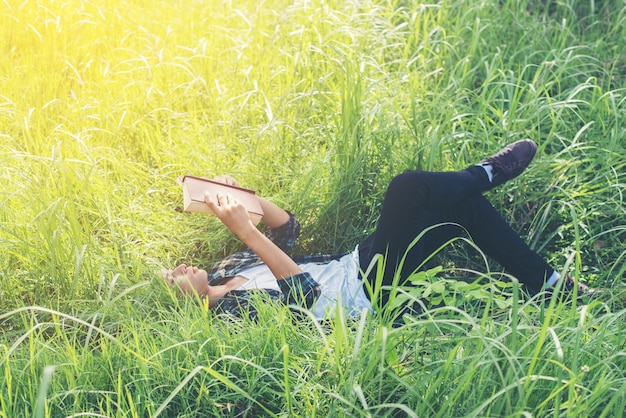 Relaxed young man reading outdoors Free Photo