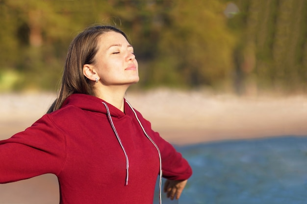 Relaxed young woman breathes fresh air in nature on the beach Premium Photo