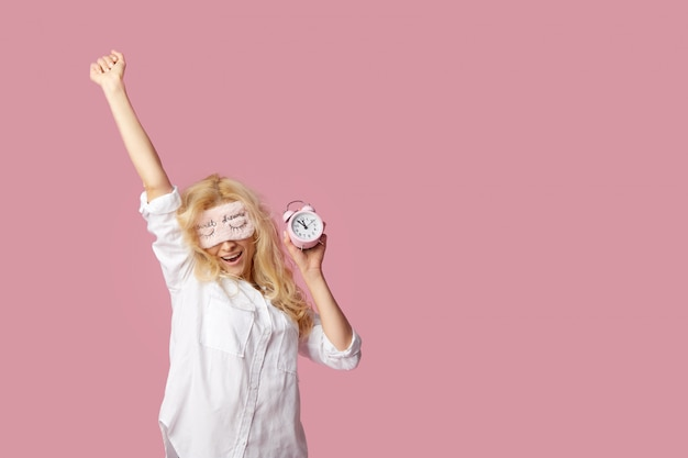 Relaxed young woman in pajamas and sleep masks on a pink wall. alarm clock woke up the girl Premium Photo