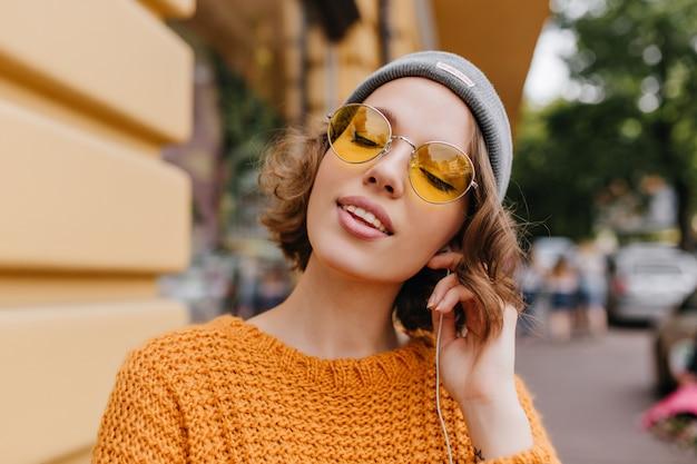 Расслабленная молодая женщина с бледной кожей, наслаждающаяся музыкой с закрытыми глазами, стоя на фоне улицы Бесплатные Фотографии