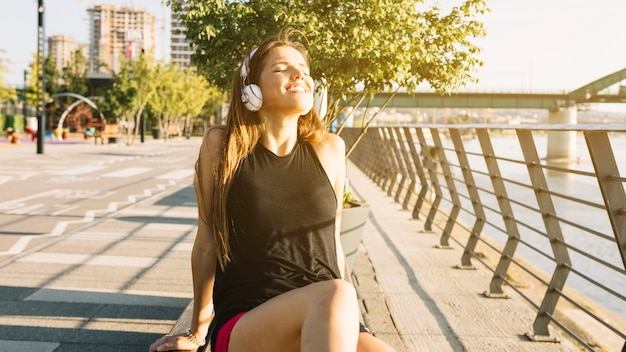Relaxed женщина, слушать музыку на наушники на открытом воздухе Бесплатные Фотографии