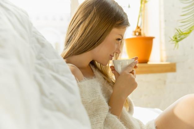 家でリラックス。暖かい日光とソファに横たわって美しい若い女性 無料写真