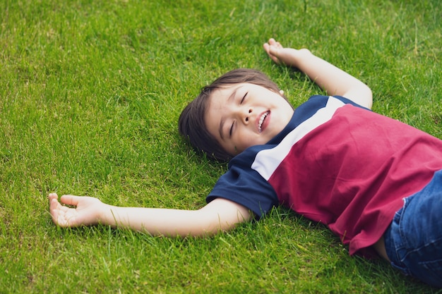 Relaxing child closing his eyes and laughing while lying down on green grass in the park Premium Photo