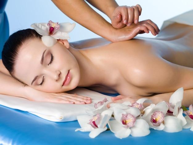 Расслабляющий массаж спины для молодой красивой женщины в спа-салоне - горизонтальный Бесплатные Фотографии